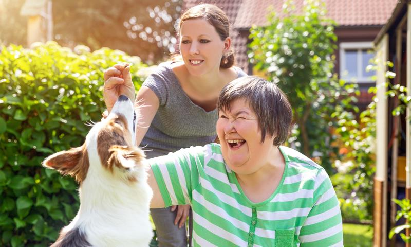Older Mother And Daughter In Garden With Dog