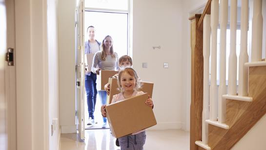Young Family Moving In Children With Boxes